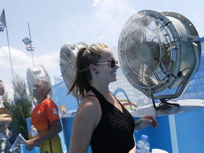 Asistentes a un torneo deportivo se refrescan frente a unos ventiladores.