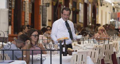 Un camarero atiende una mesa en un restaurante de Ronda (Málaga).