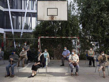 Un grupo de vecinos espera su turno de vacunación en el colegio público Carmela Carvajal, en Santiago de Chile.