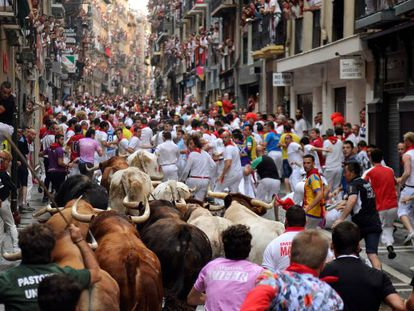 Un grupo de corredores avanza delante de los toros a su paso por la calle Estafeta, en Pamplona, en 2016.