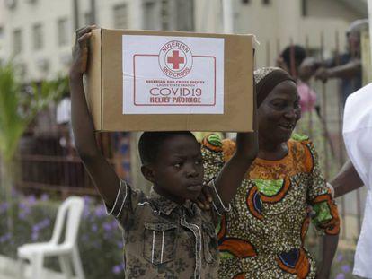 Un niño y su madre en el suburbio de Makoko, en Lagos, transportan una caja con comida que han recibido de la Cruz Roja nigeriana el pasado domingo.