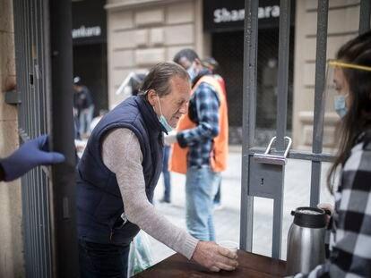 Un hombre recoge comida en la parroquia de Santa Anna.