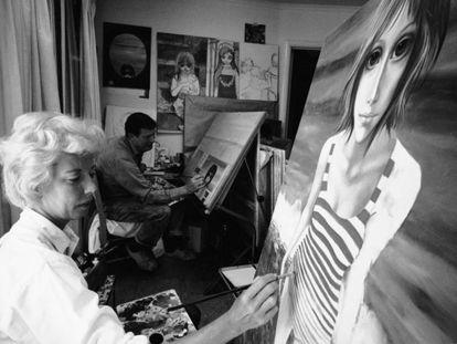 Margaret Keane pintando, en 1965, sus características figuras de ojos grandes. Al fondo, su marido Walter, que se llevó toda la gloria. Tim Burton contó la historia en la película 'Big eyes' (2014), protagonizada por Amy Adams.