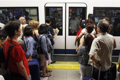 Un grupo de viajeros aguarda la apertura de puertas de un vagón en la estación de Nuevos Ministerios.