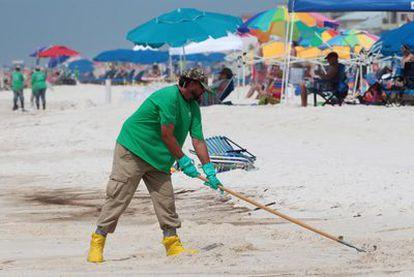 Un operario de limpieza pasa el rastrillo por la playa de Orange Beach en Alabama (EE UU), una de las afectadas por el vertido de petróleo de BP en el golfo de México.
