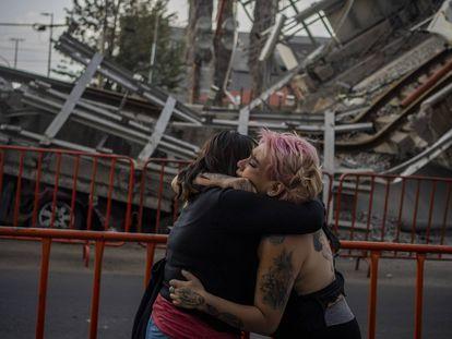 Dos mujeres lloran la muerte de una amiga tras el derrumbe en la Línea 12 del metro en Ciudad de México.