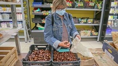 Una mujer compra comida de proximidad a granel en el supermercado cooperativo La Osa, en Madrid.