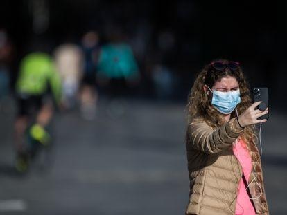 Una mujer con mascarilla se hace una foto con el móvil en el segundo día de desconfinamiento en Madrid.