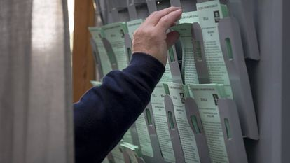 Un hombre recoge la papeleta en una cabina de un colegio electoral en Sevilla.