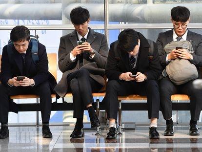 Varias personas usan el móvil en una feria de empleo, en Seúl en 2018.
