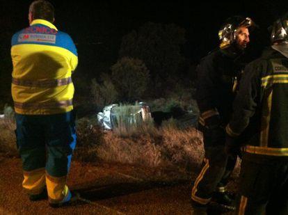 Un sanitario observa el todoterreno accidentado tras caer por el barranco de 10 metros.