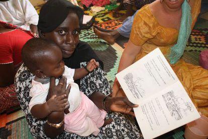 Una de las alumnas aprende a leer con un libro ilustrado.