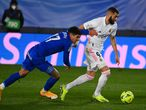 Getafe's Uruguayan defender Mathias Olivera (L) challenges Real Madrid's French forward Karim Benzema during the Spanish league football match between Real Madrid CF and Getafe CF at the Alfredo di Stefano stadium in Valdebebas, on the outskirts of Madrid on February 9, 2021. (Photo by GABRIEL BOUYS / AFP)