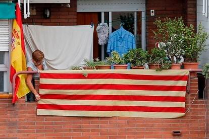 Una mujer coloca la bandera catalana en un balcón de Barcelona vecino a otro del que cuelga la de España.