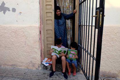 Latifa junto a sus dos hijos en la puerta de su casa en Melilla.