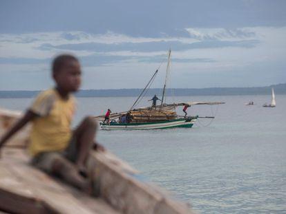 Varias personas transportan madera en una embarcación frente a la costa de Paquitequete, en Mozambique.