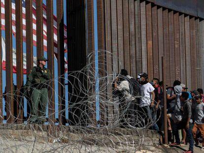 Inmigrantes en la valla fronteriza de Tijuana, México.