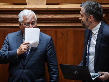 El primer ministro, António Costa, se tapa la cara mientras habla con el ministro de Infraestructuras, Nuno Santos, durante el debate para prorrogar el estado de emergencia en Portugal.