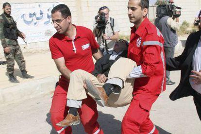Miembros de la Media Luna Roja trasladan a un ciudadano durante una operación de evacuación en Muadamiya, una zona rural de Damasco.