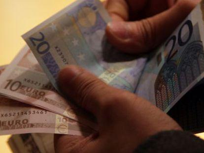 Un hombre cuenta billetes de euro en 2011.