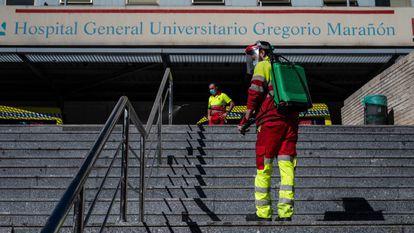 Un operario desinfecta el pasamanos de la escalera de la entrada principal del hospital Gregorio Marañón.