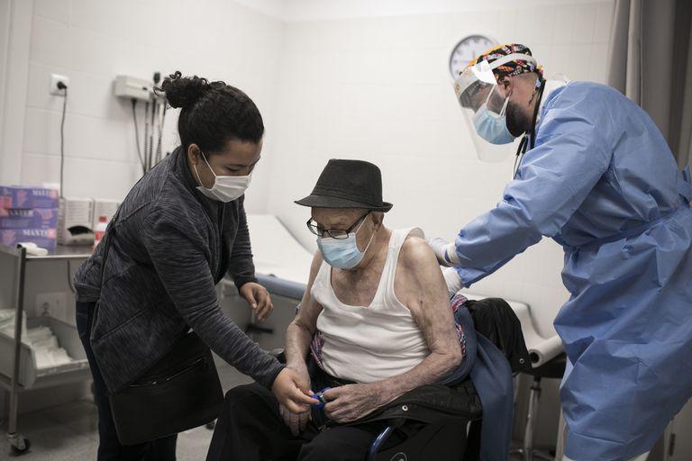 En la imagen, el doctor Gerard Suárez atiende a Rafael, de 96 años, que está acompañado de su cuidadora, Ana.