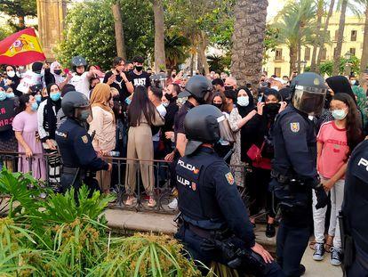 Miembros de la Policía Nacional ante un grupo de manifestantes congregados en Ceuta, este lunes.