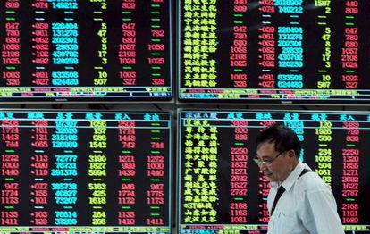 Un inversor chino junto a una pantalla de cotizaciones.