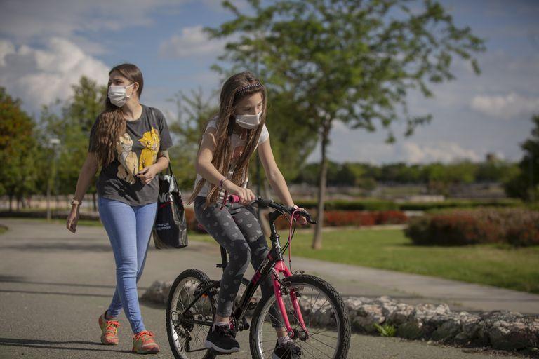 Una mujer y su hija pasean por un parque de Sevilla, este martes.