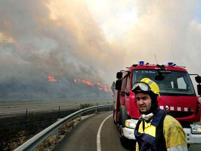 Un efectivo del cuerpo de bomberos observa en la AP-7 las llamas del incendio forestal declarado hacia las 13 horas en La Jonquera (Girona).