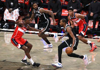Kevin Durant, con el balón, ante Thomas Bryant, en el Nets-Wizards.