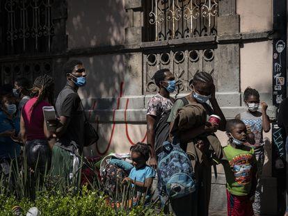 Un grupo de haitianos hacen fila a las afueras de la Comisión Mexicana de Ayuda a Refugiados (COMAR) de la Ciudad de México para solicitar asilo humanitario.