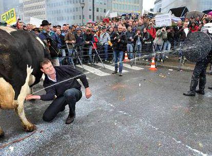Un ganadero rocía con leche a un policía durante las protestas a las puertas de la Comisión Europea.