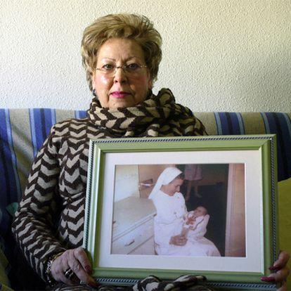 Dolores Chumillas muestra una foto de su hija en brazos de una monja tras dar a luz en 1978.
