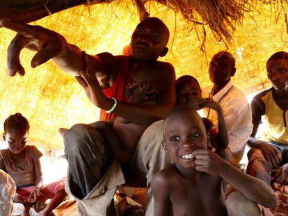 Sylvin Boda señala con el dedo junto a varios de sus vecinos y algunos de sus hijos, en Betare-Oya (Camerún).