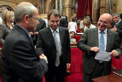 El presidente catalán, José Montilla (izquierda), da la mano al líder de CiU, Artur Mas, ayer en el Parlamento catalán.