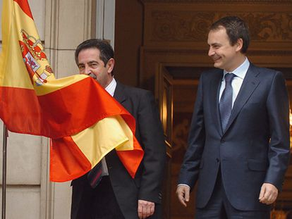 El presidente de Cantabria, Miguel Ángel Revilla, besa la bandera española junto a José Luis Rodríguez Zapatero.