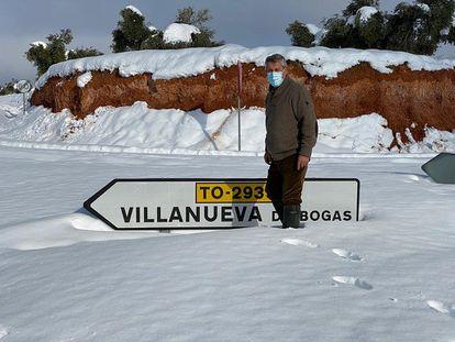 Un vecino de Villanueva de Bogas (Toledo) frente al rótulo de acceso al pueblo, semicubierto de nieve.