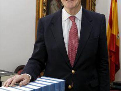 El director de la Real Academia de la Historia, Gonzalo Anes, posa junto a varios tomos del Diccionario Biográfico Español.