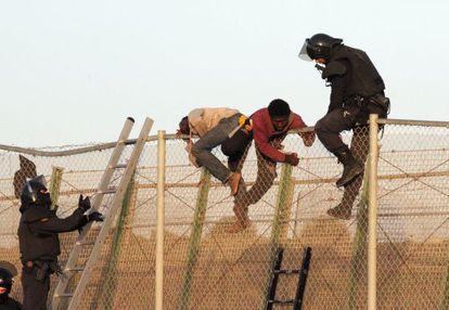 Un agente junto a dos inmigrantes en la valla.