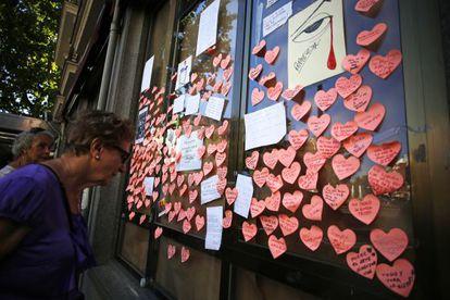 Una mujer lee los mensajes de despedida pegados las cristaleras del local