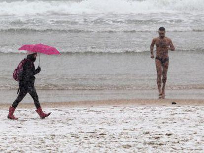 Un hombre en bañador corre por una nevada playa de la Concha, en San Sebastián.