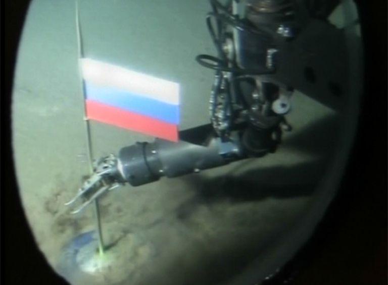 El brazo mecánico de uno de los batiscafos planta la bandera rusa en el fondo marino polar.