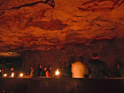Visitantes en la neocueva de Altamira iluminada con lámaras de tuétano.