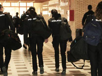 Varios alumnos de la Escuela de la Policía Nacional de Ávila caminan por un pasillo de su sede.