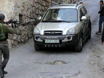 Un soldado israelí detiene un vehículo palestino en Hebrón, este martes.