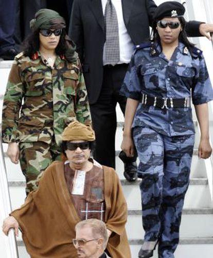 Gadafi, escoltado por su guardia de seguridad femenina en el aeropuerto de Ciampino, cerca de Roma, en 2010.