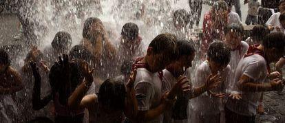 Varios niños con ropa de sanfermines reciben agua durante un encierro infantil en las colonias de verano de 2008 en Getaria, País Vasco.