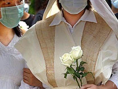 La viuda de un enfermero muerto por la neumonía en Hong Kong, en  el entierro del marido.  / AP