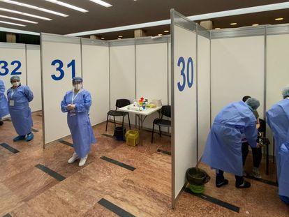 Un hombre recibe la vacuna de Pfizer mientras el personal médico espera a los pacientes en una sala de eventos en Bucarest, Rumanía.